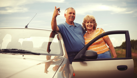 two older couple outside their car
